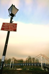 Bridge on the River Thames (Peter Denton) Tags: uk bridge red england london lamp sign thames warning river notice tide eu landmark richmond kingston lamppost suspensionbridge tidal hamptoncourt teddington londonist canoneos400d peterdenton