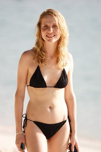 Smiling Blonde Girl In Black Bikini Walking On Beach