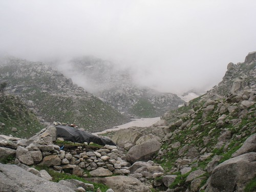 Clouds shroud the mountain and ridge. Rock shelter is in foreground.