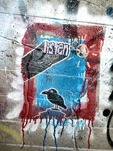 graffiti: a black bird in a blue window, with the word 'listen' pushing out overhead