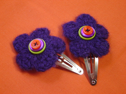 hair clips is decorated is two purple crocheted and flowers. buttons are lime, purple, and orange.