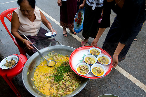 Serving up bowls of khua kai, a thick chicken curry, at a funeral in Luang Prabang