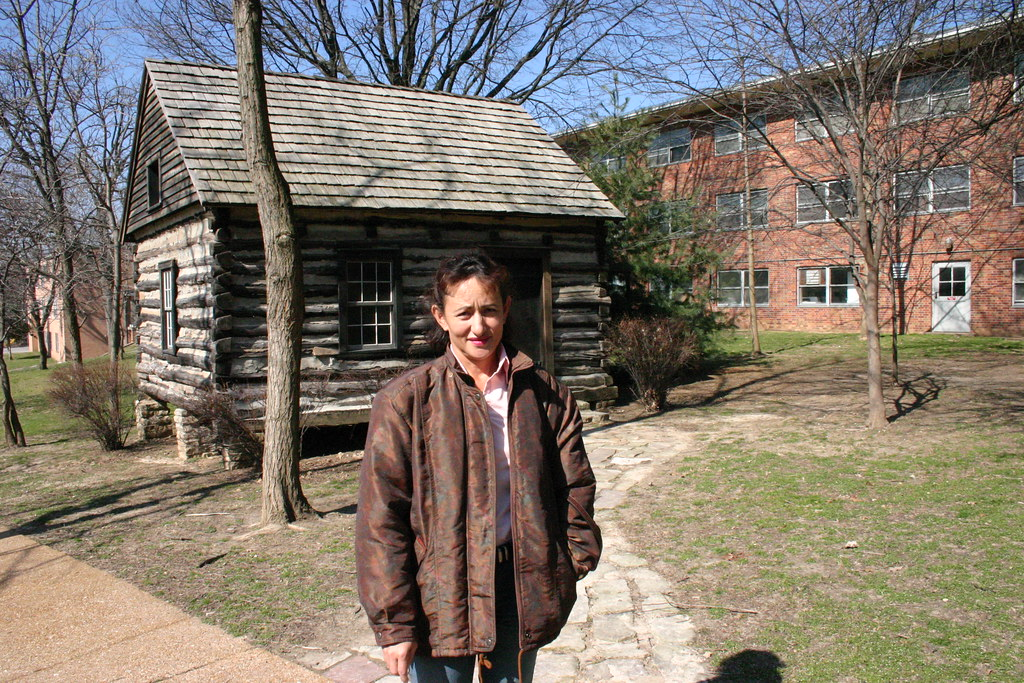 Luz Maria in front of the log-cabin seminary