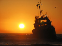 Shipwreck Sunset (biancapreusker) Tags: ocean sunset sea orange sun beach water silhouette cormorants lost evening coast boat waves ship shipwreck transportation wreck namibia swakopmund walvisbay bigmomma canonpowershots2 photofaceoffplatinum pfogold thechallengefactory