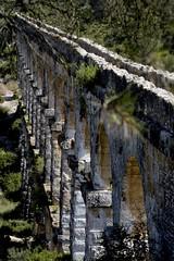 Tarragona's ancient aqueduct  Rob Watkins 2004 (Aland Rob) Tags: old trees sun rome monument water high spain ancient arch roman decay arches catalonia aqueduct valley carry bleached tarragona tarraco perpective photographrobwatkins landscapesshotinportraitformat
