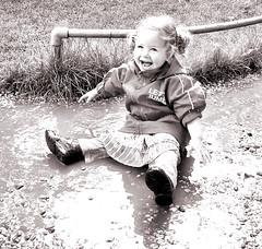 Madeliefje in de plas. (ei) Tags: blackandwhite sepia fun child zwartwit lol kind laugh lachen madelief thechallengegame challengegamewinner