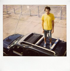 Roof party. (Claire Marie Vogel) Tags: roof boy man film look car yellow standing square polaroid stand photo claire waiting nissan looking bright top parking lot photograph instant hood shorts spectra vogel xterra mikal cronin