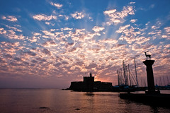 sunrise (esther**) Tags: morning blue light sea sky sun lighthouse reflection clouds sunrise boats bravo view greece sunrays rhodes interestingness180 interestingness58 interestingness38 interestingness130