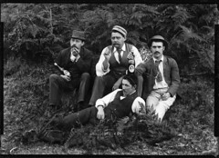 Four well-dressed men holding beer bottles (Powerhouse Museum Collection) Tags: portrait white man black fern men beer grass pose ties blackwhite funny bottles label lounge caps group pipes pipe ale hats smoking moustache cigars lounging amusing smoker dandy necktie mustaches powerhousemuseum beerbottle looe indiapaleale lanecove princeofwales 1896 pipesmoker pocketwatches xmlns:dc=httppurlorgdcelements11 dc:identifier