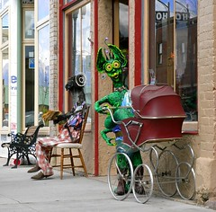 Salida, Colorado - Strangers are welcome! (Shamus O'Reilly) Tags: wood sculpture usa baby silly art statue paper fun reading weird fantastic colorado funny pavement alien humor surreal goat humour plaster rubber aliens plastic sidewalk mum fantasy clay salida monsters creatures varmints pram chaffeecounty bungledjungle patlandreth suzannemontano