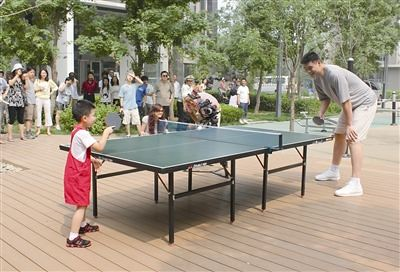 June 20, 2011 - Yao Ming plays table tennis with a 6 year old boy as part of a promotional video for China National Fitness Day
