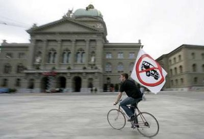 A man on a bicycle holds a flag protesting against off-road cars, in front of the parliament building in Bern