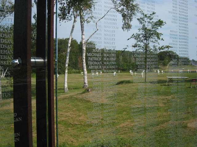 15 - Memorial with the names of Irish dead with cemetery in the background, on Grosse Ile