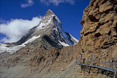 matterhorn approach (Ron Layters) Tags: leica orange cliff mountain clouds geotagged switzerland path walk slide bluesky velvia transparency zermatt matterhorn fujichrome wallis catwalk valais cervin gantry cervino morraine mountainsalps elevation40004500m altitude4478m summitmatterhorn montcervin 4478m mattertal ronlayters ronet slidefilmthenscanned elevatedwalkway hornlihut hornliridge 14692ft leicar3flickrfly approachpath shestakingitup stoneyshoulder whatamountain geo:lat=45988464 geo:lon=7694077