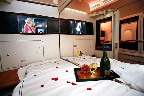 Interior de una suite en el Airbus A380, sábanas blancas, champagne, fresas y películas