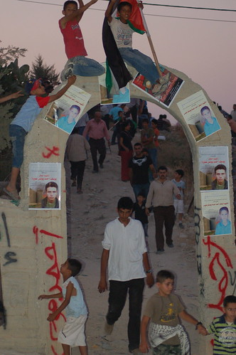 Kids in Ni'lin sit on the cemetery arch, while mourners exit the funeral