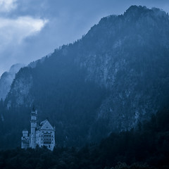 A castle in the mountains (manganite) Tags: blue sky mountain castle topf25 monochrome clouds digital germany dark square landscape geotagged bayern bavaria nikon europe mood tl atmosphere monotone d200 nikkor dslr toned neuschwanstein schloss vignette hohenschwangau schwangau 18200mmf3556 utatafeature manganite nikonstunninggallery repost1 date:year=2008 date:month=september date:day=19 geo:lat=47555387 geo:lon=10736293 format:orientation=square format:ratio=11 repost2