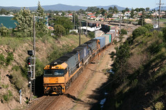 Pacific National diesel electric locomotives NR20 + NR57 + NR112 work a down container freight train pass the tiny railway station at Telerah, NSW Australia.