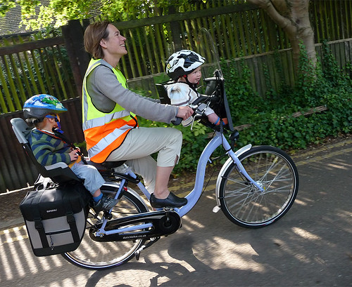 Mum with two kids on one bike by Dee Railer.