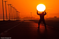 Critical moment!! (Khalid AlHaqqan) Tags: road sunset orange sun man guy silhouette standing canon way stand holding bars zoom wires kuwait khalid soe 100400mm carry hold flickrsbest 40d mywinners abigfave kuwson platinumphoto alhaqqan theunforgettablepictures canon40d khalidalhaqqan