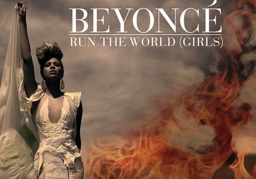 Beyonce, outside with flames behind her, stands up straight in a white feathered dress. The words 'Run the World (Girls)' are behind her in white text, as is her name.