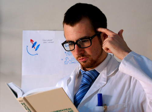 Photo of a scientist puzzling over a math book