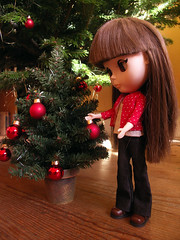 Decorating her tree with red balls