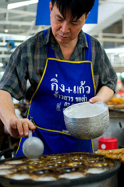 Mr Tii making khanom khrok, crispy coconut puddings as he's done for more than 25 years at Or Tor Kor Market, Bangkok