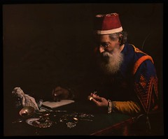 Costumed man examining jewelry (pawnbroker?) (George Eastman House) Tags: costume jewelry georgeeastmanhouse autochrome williamsimon photo:process=colorplatescreenautochromeprocess color:rgb_avg=2315d drwsimon drwilliamsimon geh:accession=198300630003