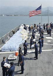 US sailors loading humanitarian cargo on the deck of guided-missile destroyer USS McFaul