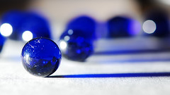 The Only One, Of Many (BluAlien) Tags: blue light shadow macro glass closeup nikon dof bokeh widescreen sb600 sphere ttl marble 169 16x9 d40 offcameraflash singintheblues 105mmvr ttlcord sc28 afs105mm28vr