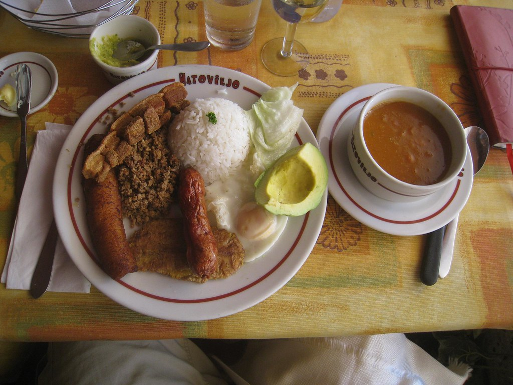 The oversized Bandeja Paisa is a popular dish in Antioquia, consisting of: beans, white rice, ground meat, pork rind (chicharron), fried egg, plantains, chorizo, arepa, and avocado.