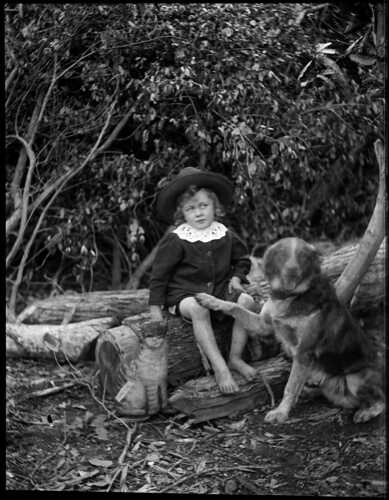 Bare foot boy wearing a hat, seated on a log by Powerhouse Museum Collection.
