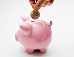 Hand Putting Deposit Into Piggy Bank