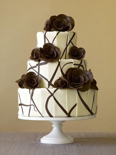 A gorgeous, modern, white and brown tiered wedding cake with modern roses.