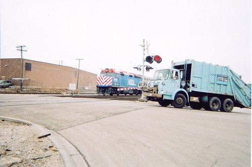 A City of Chicago Department of Streets and Sanitation garbage truck, and a westbound Metra commuter train at the North Kilbourn Avenue RR crossing. Chicago Illinois. April 2006. by Eddie from Chicago