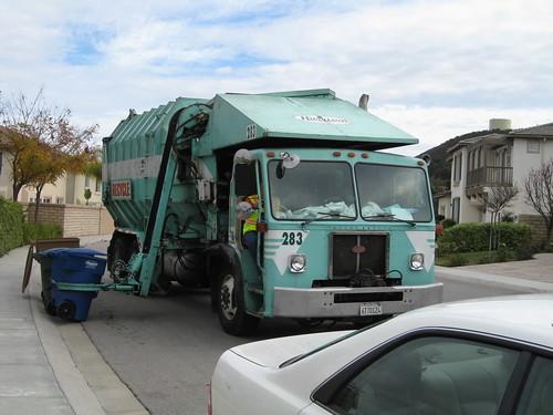 垃圾車的機械手臂抓住垃圾桶