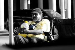 Hawaiian Punch (eflon) Tags: road bw guy yellow beard holding sitting side homeless selectivecolor baseballcap