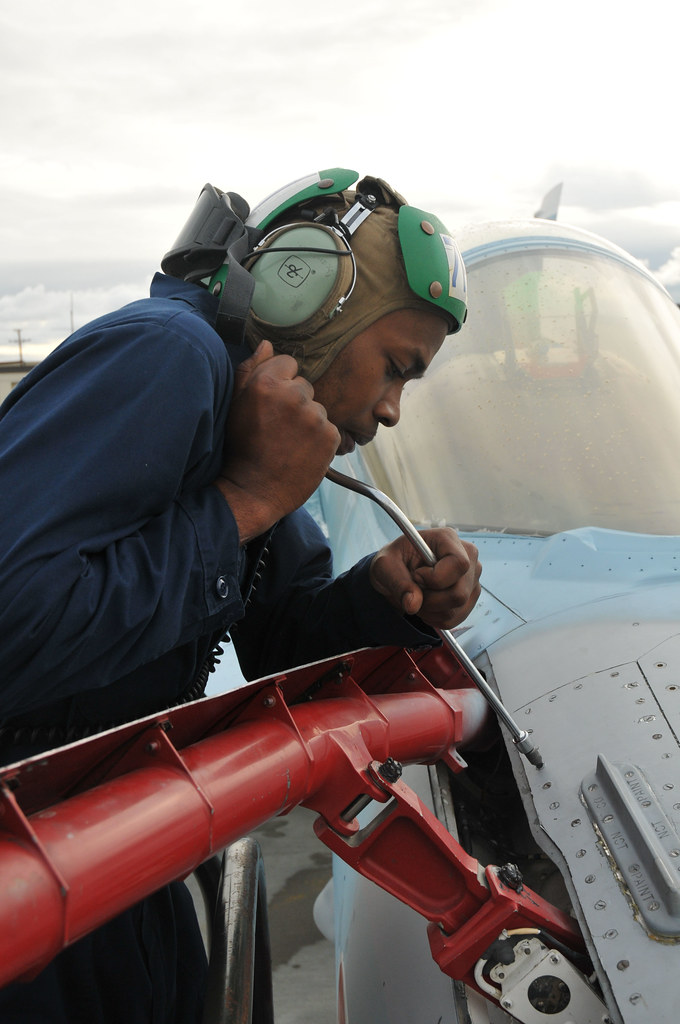 Sailor completes maintenance on the in-flight refueling probe of an F/A-18C Hornet