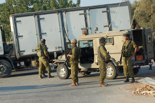 At Yousef's funeral, the Israeli Army stands guard over the entrance to Ni'lin