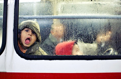 Child starring through the window and making funny face (Ivan Radic) Tags: vienna city street people night tram colour ivan radic mobformat11decisivemoment ivanradic child starringthroughthewindow makingfunnyface
