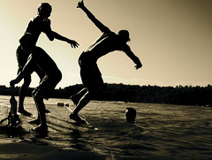 brotherly love (leslie m k) Tags: sunset sky people bw lake black reflection men boys water sepia wisconsin contrast swimming fun happy evening blackwhite jump joy silhouettes guys push raft upnorth outline