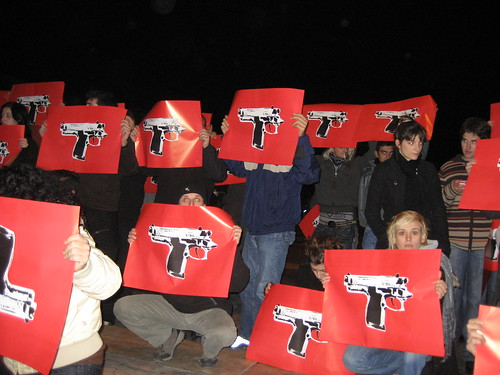 Protesters holding photoshopped image of gun to protest police shooting