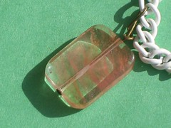 a pendant on a bracelet on green