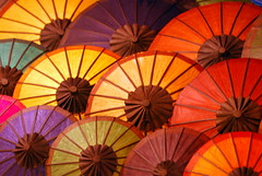 waiting for the rain (pranav_seth) Tags: color colors night umbrella asia southeastasia market south silk vivid nightmarket laos umbrellas lao luang prabhang vividmasters luangprabhng