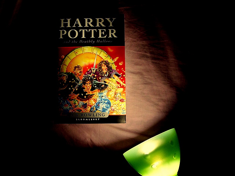 A photograph of the seventh Harry Potter book shrouded in darkness, lit from the bottom right corner by a green lamp.