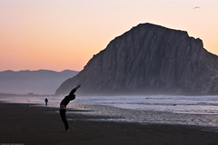 Man performs mystical stretching exercises on Morro Strand (by mikebaird)