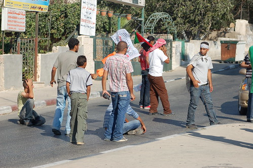 Kids from Ni'lin first sat, then lied down in the road to protest the PA roadblock