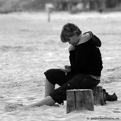 Text On The Beach (Clockwork Noggin) Tags: wood people bw woman beach monochrome mobile suffolk sand sitting phone legs candid streetphotography sit hood seated groyne southbeach texting lowestoft kirkley blackwhitephotos canoneos400d clockworknoggin
