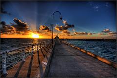 St Kilda sunset (Luke Tscharke) Tags: sunset sky orange clouds digital canon geotagged eos pier shadows dusk australia melbourne victoria railing vignette 2009 hdr xsi sigma1020mm 3xp 450d digitalrebelxsi lushaki luketscharke geo:lat=3786458 geo:lon=14496799